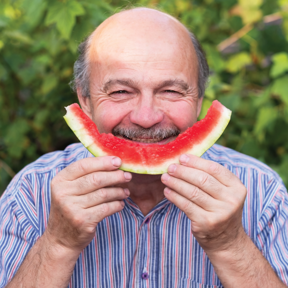 Man holding slice of watermelon in front of his face like a smil.